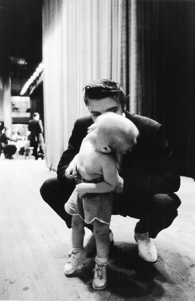 1956 bending down kiss young child